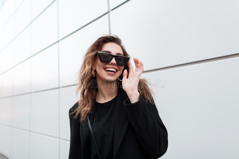 Mujer joven alegre bonita del inconformista en gafas de sol elegantes con una sonrisa en una capa negra de moda que presenta al a foto de archivo