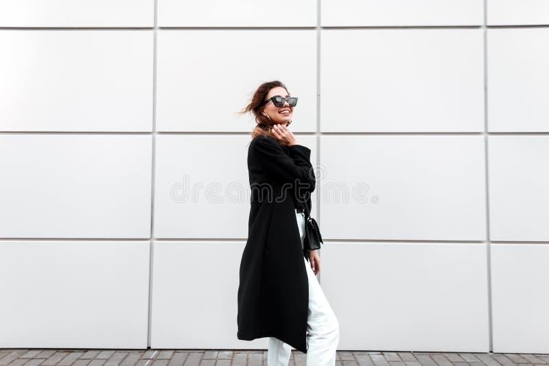 Mujer joven alegre bonita del inconformista en una capa larga negra del vintage en los vaqueros blancos con un bolso de cuero ele fotografía de archivo