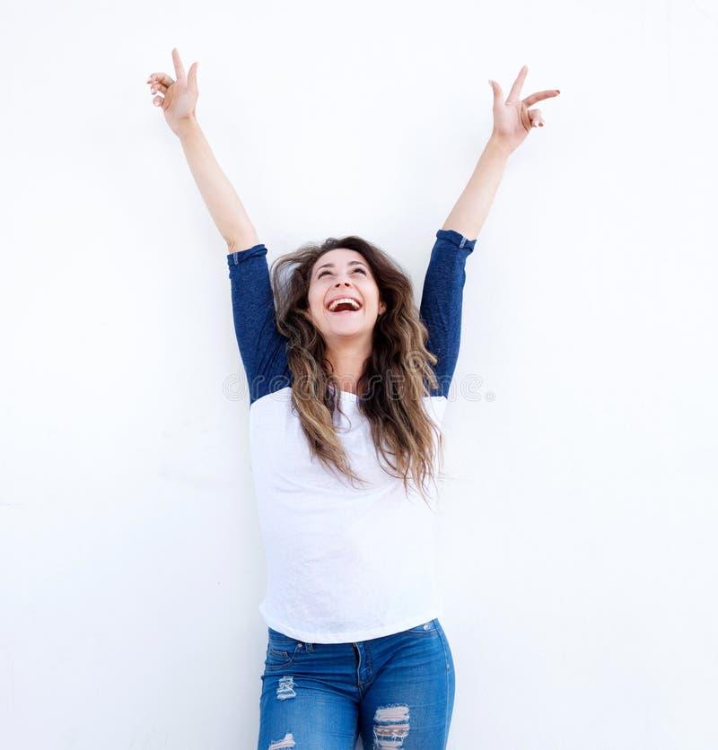 Mujer joven alegre con los brazos aumentados y que miran para arriba imágenes de archivo libres de regalías