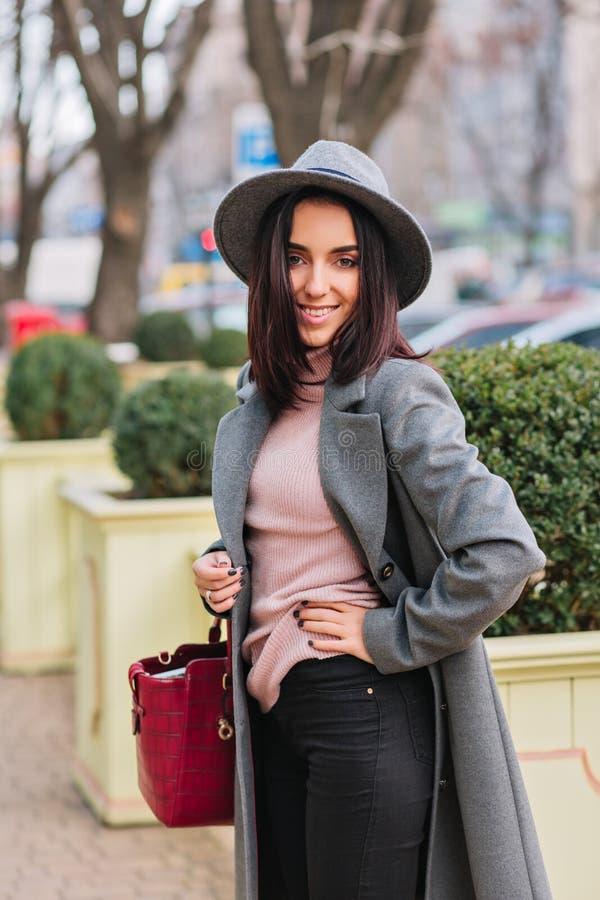 Mujer joven alegre elegante en la capa gris larga, sombrero caminando en la calle en ciudad en fondo del parque Ropa de lujo foto de archivo libre de regalías