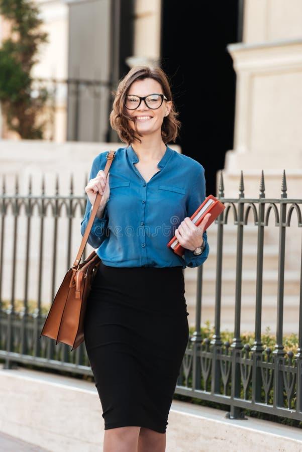 Mujer joven alegre en las gafas de sol que sostienen la libreta foto de archivo