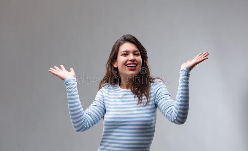 Mujer joven alegre feliz que gesticula con sus manos imagenes de archivo