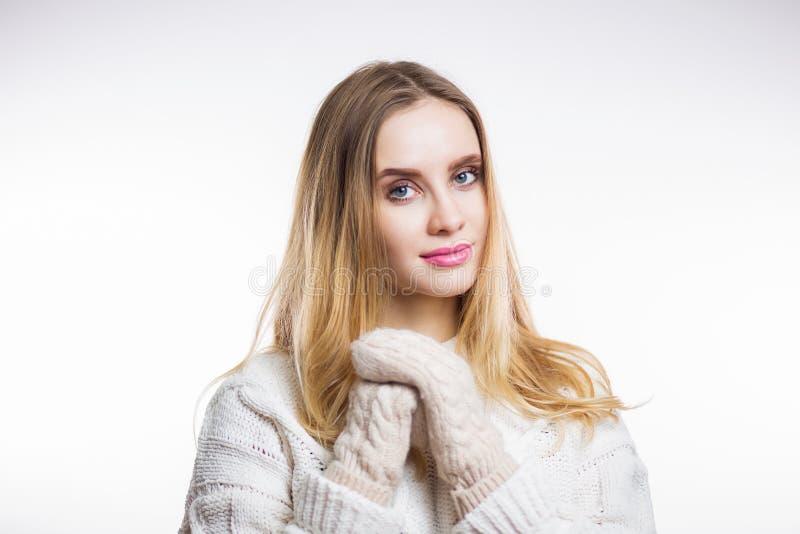 Mujer joven alegre feliz que lleva el suéter y las manoplas beige calientes hechos punto y miradas en la cámara en el fondo blanc fotografía de archivo libre de regalías