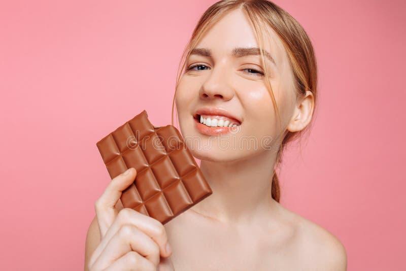 Mujer joven alegre hermosa que sostiene una barra del chocolate negro en un fondo rosado imagen de archivo libre de regalías