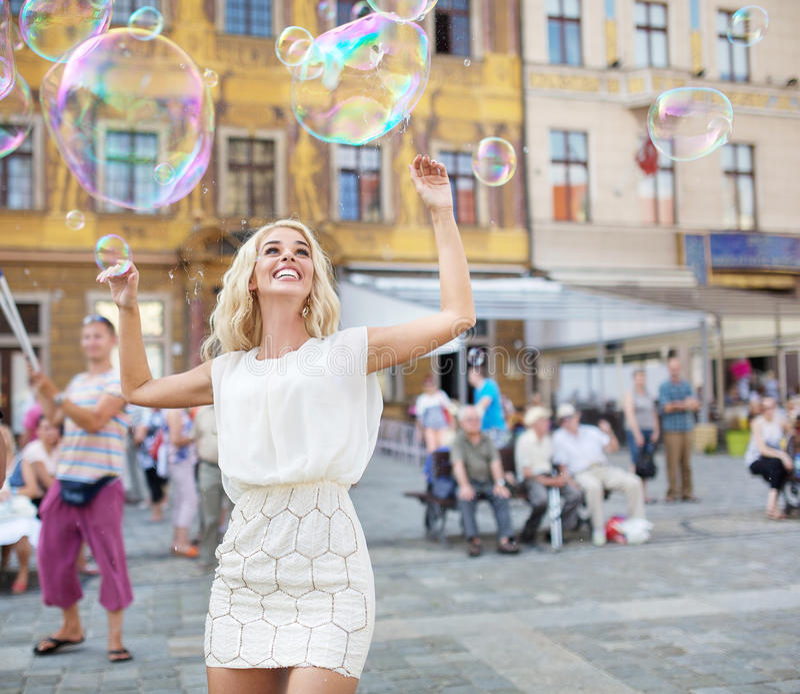 Mujer joven alegre que coge las burbujas de jabón imagenes de archivo