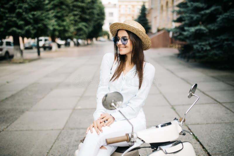 Mujer joven alegre que conduce la vespa en la calle de la ciudad foto de archivo libre de regalías