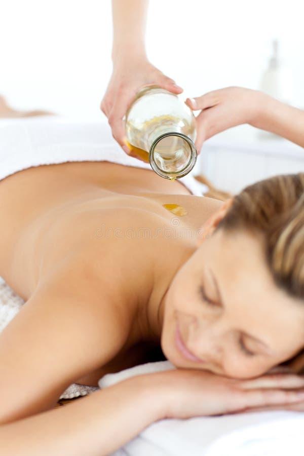 Mujer joven alegre que disfruta de un masaje posterior con petróleo foto de archivo