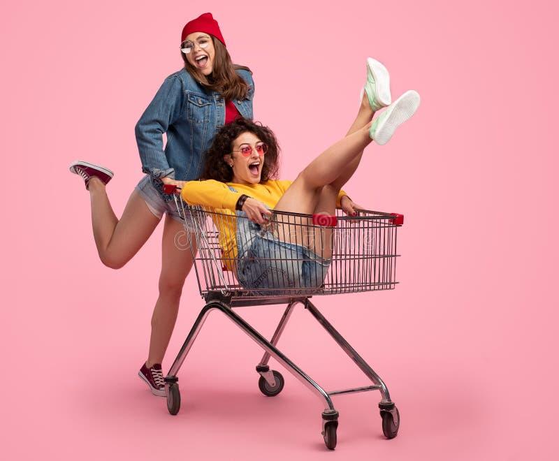 Mujer joven alegre que empuja el carro de la compra con el amigo fotos de archivo libres de regalías
