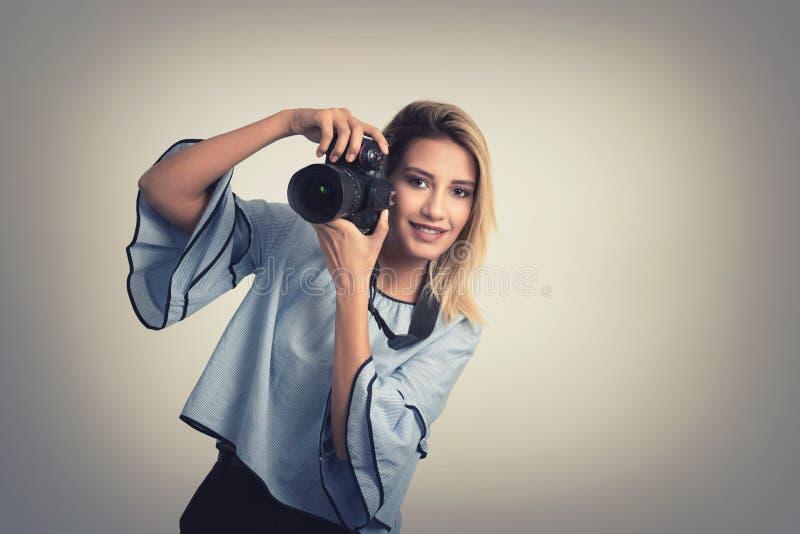 Mujer joven alegre que hace la foto en cámara sobre fondo gris fotos de archivo