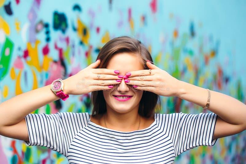 Mujer joven alegre que la cubre ojos con sus manos con un NIC foto de archivo