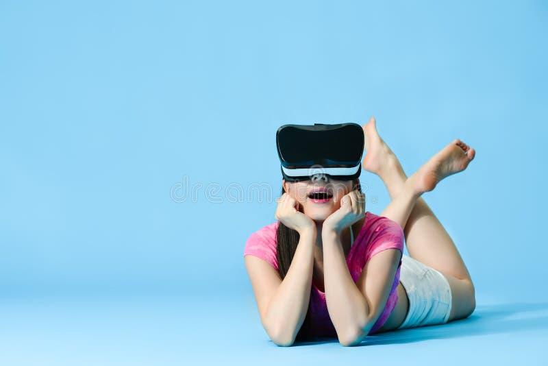 Mujer joven alegre que lleva los vidrios del dispositivo de VR fotos de archivo