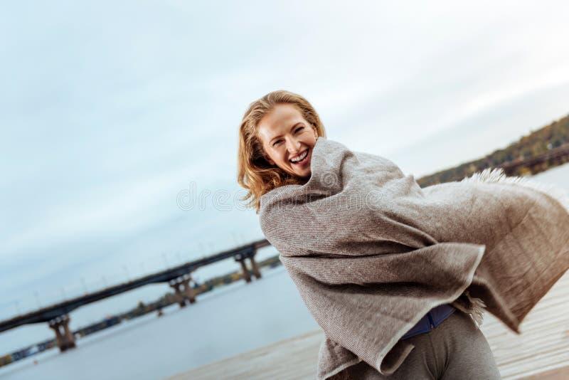 Mujer joven alegre que lleva una tela escocesa cerca del agua imagen de archivo