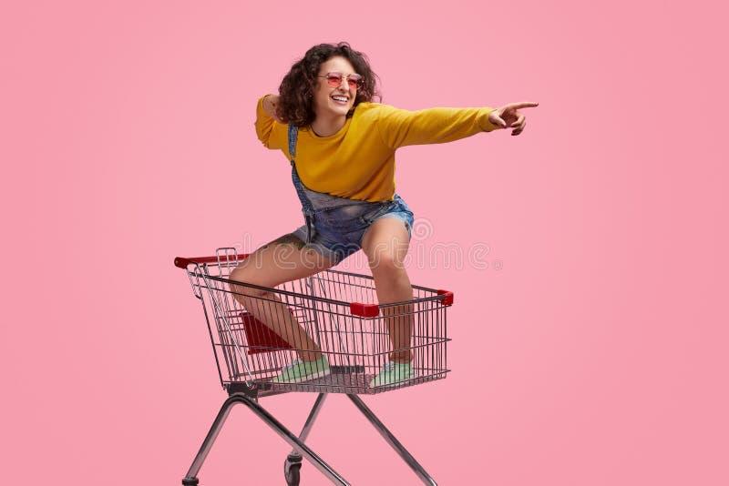 Mujer joven alegre que monta adelante en el carro de la compra fotos de archivo libres de regalías