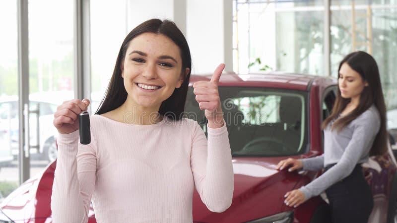 Mujer joven alegre que muestra los pulgares que detienen llaves del coche imagen de archivo libre de regalías