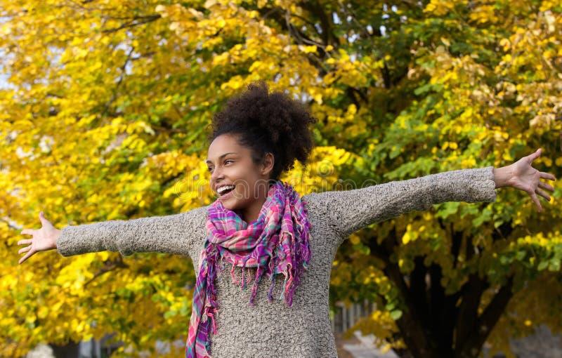 Mujer joven alegre que se coloca al aire libre con los brazos extendidos fotos de archivo