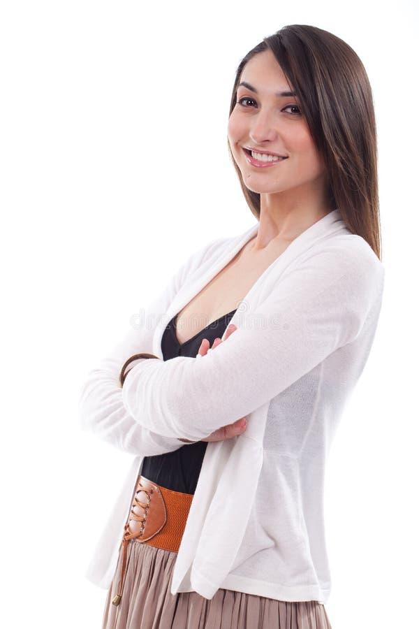 Mujer joven alegre que se coloca con los brazos cruzados foto de archivo