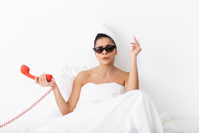 Mujer joven alegre que se sienta en cama despu?s de ducha fotos de archivo libres de regalías