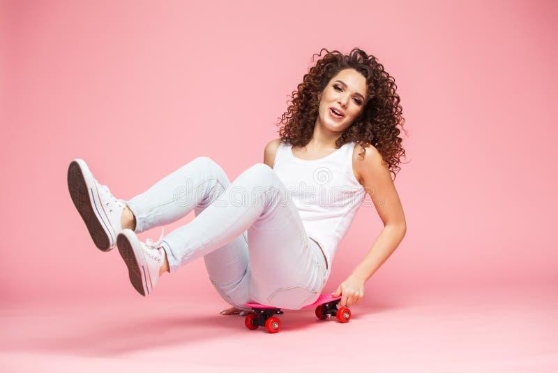 Mujer joven alegre que se sienta en el monopatín y que se divierte sobre fondo rosado foto de archivo