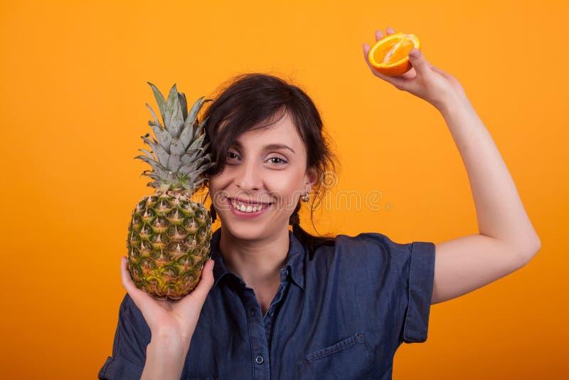 Mujer joven alegre que sonríe y que muestra las frutas exóticas en la cámara en estudio sobre fondo amarillo imagen de archivo