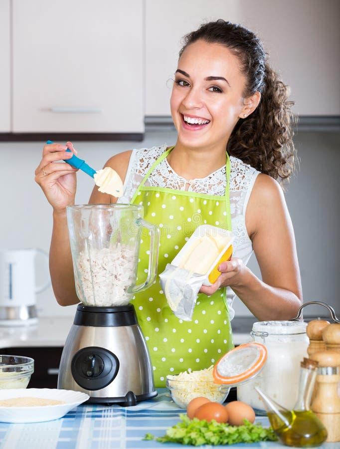 Mujer joven alegre que usa la licuadora de la cocina imagenes de archivo