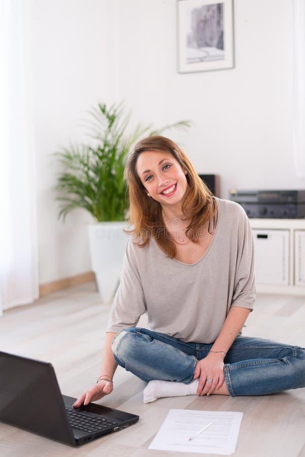 Mujer joven alegre relajada en casa con el ordenador portátil foto de archivo libre de regalías
