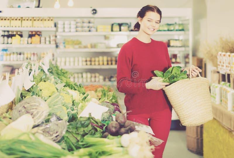 Mujer joven amistosa que elige verduras estacionales en tienda de la granja fotos de archivo