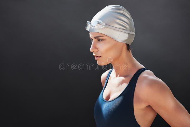 Mujer joven apta en el traje de natación que mira lejos imagen de archivo