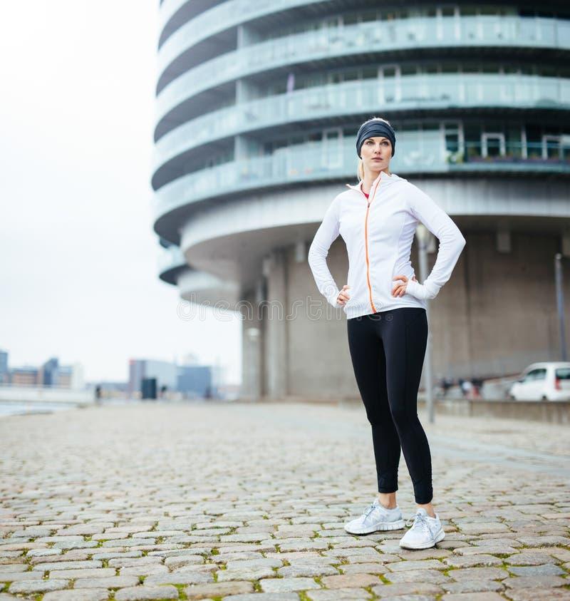Mujer joven apta en la ropa de deportes que se coloca en la calle fotos de archivo