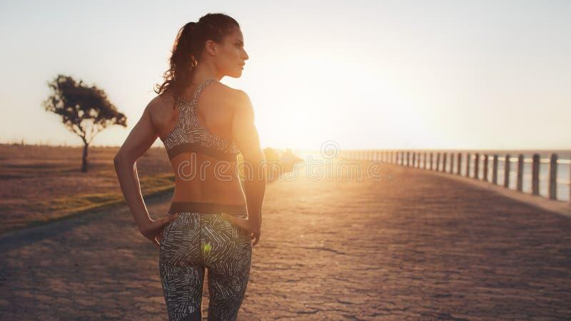 Mujer joven apta que camina en la 'promenade' de la playa en puesta del sol fotografía de archivo