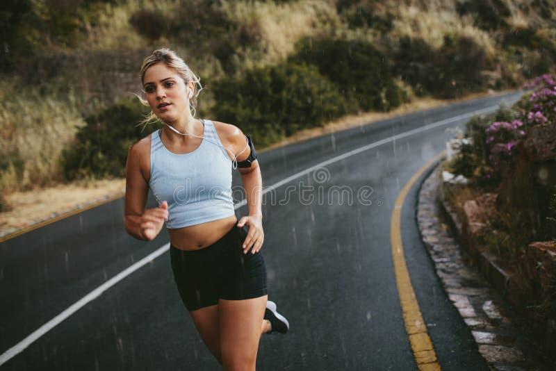 Mujer joven apta que corre en la carretera fotos de archivo