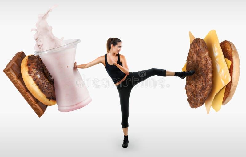Mujer joven apta que lucha apagado los alimentos de preparación rápida foto de archivo
