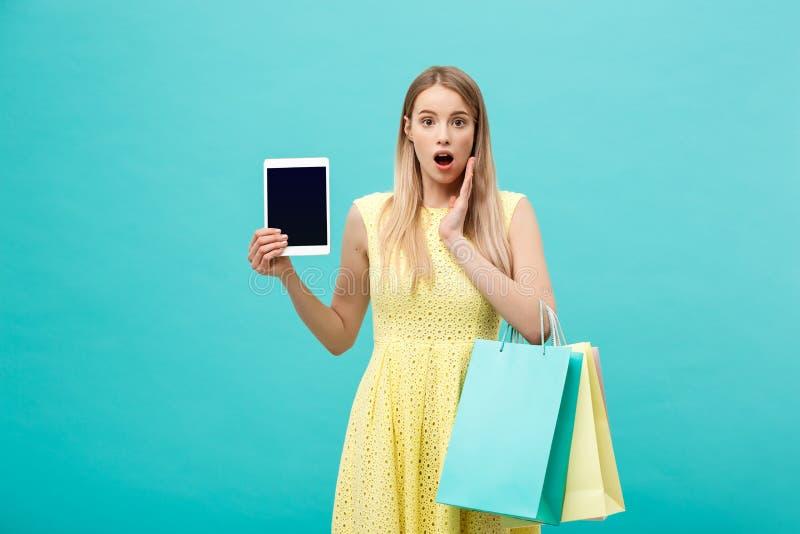 Mujer joven apuesta chocada emocionada en vestido amarillo mientras que sostiene la tableta y los panieres foto de archivo libre de regalías