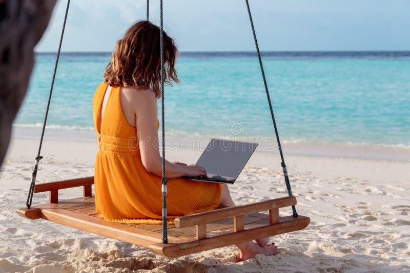 Mujer joven asentada en un oscilación y el trabajo con su ordenador portátil Agua tropical azul clara como fondo fotografía de archivo libre de regalías