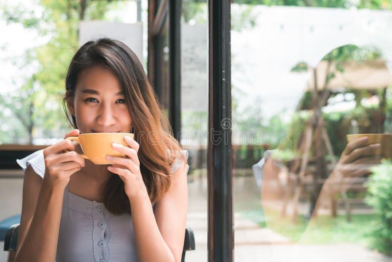 Mujer joven asiática alegre que bebe el café o el té caliente que goza de él mientras que se sienta en café imagenes de archivo