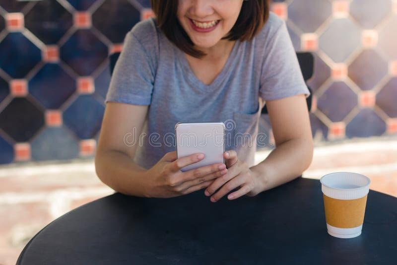 Mujer joven asiática alegre que se sienta en café de consumición del café y que usa el smartphone para hablar, la lectura y manda fotografía de archivo