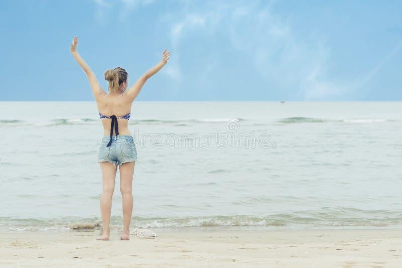 Mujer joven asiática de la libertad y de la felicidad en la playa durante viaje en día de fiesta foto de archivo