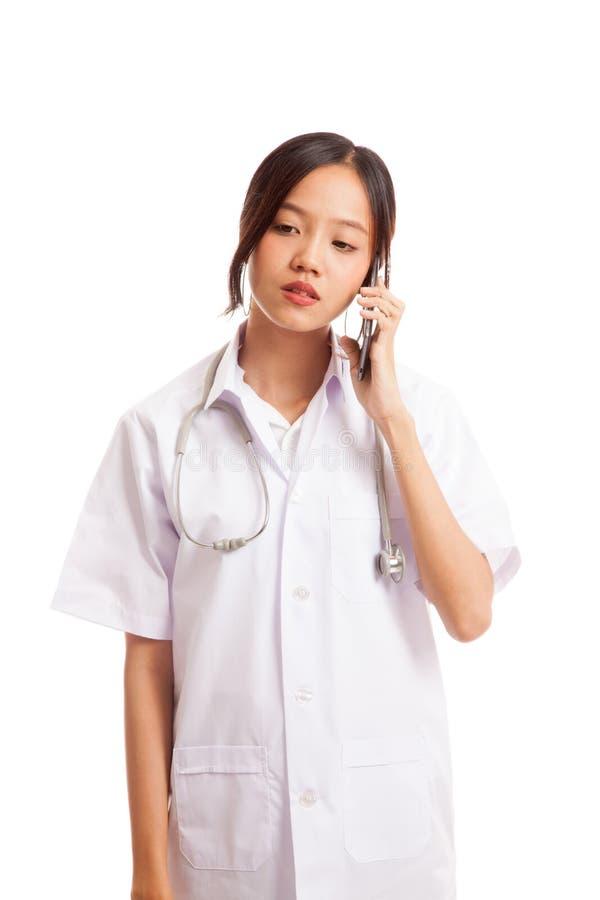 Mujer joven asiática del doctor con el teléfono móvil del uso del estetoscopio imagenes de archivo