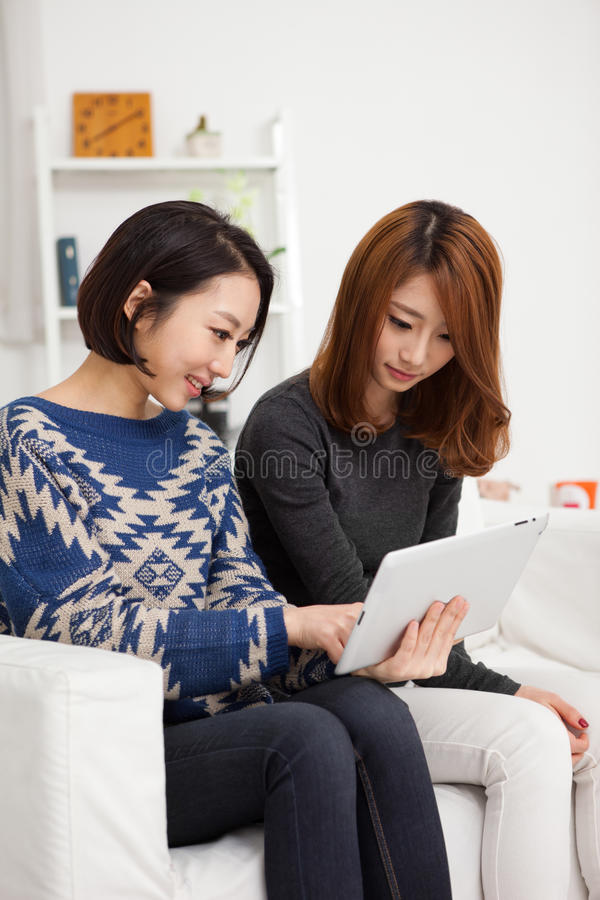 Mujer joven asiática dos que usa la PC de la tablilla. foto de archivo libre de regalías