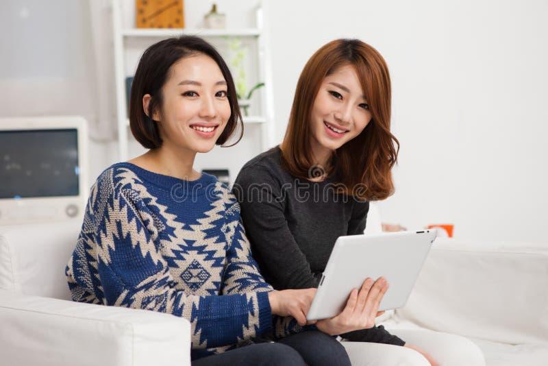 Mujer joven asiática dos que usa la PC de la tablilla. imagenes de archivo