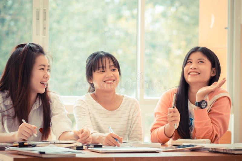 Mujer joven asiática feliz que hace estudio del grupo Universidad asiática o c imagenes de archivo