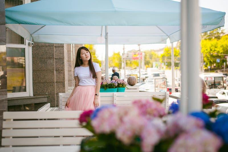Mujer joven asiática linda en café del verano al aire libre muchacha en la camiseta blanca, con el pelo largo en el interior acog fotos de archivo