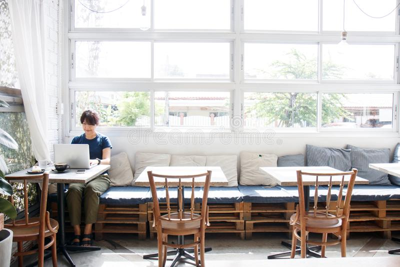 Mujer joven asiática que busca la información del viaje vía comput del ordenador portátil imagen de archivo libre de regalías
