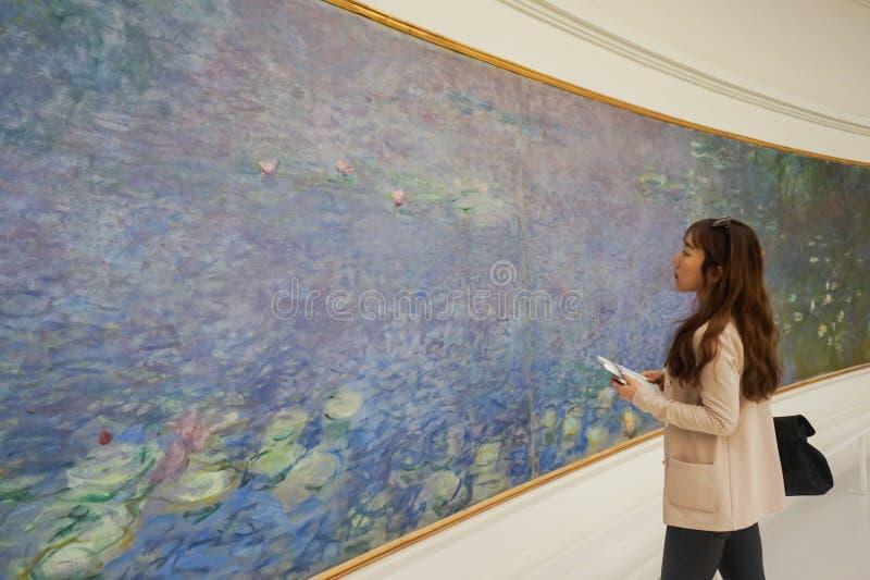 Mujer joven asiática que mira alrededor del museo del Louvre y que aprecia la belleza de una obra de arte imágenes de archivo libres de regalías