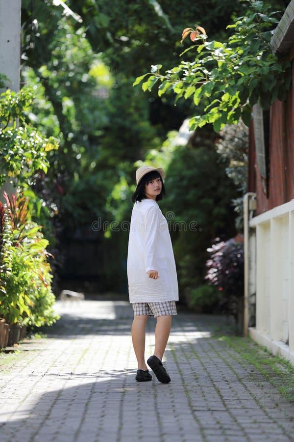 Mujer joven asiática que piensa y que mira el retrato del concepto del viaje con el fondo verde del árbol fotos de archivo libres de regalías