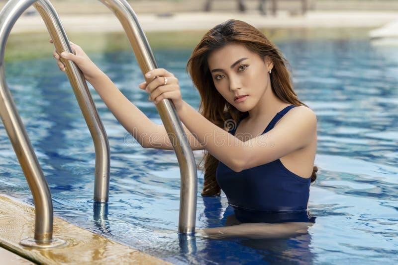 Mujer joven asiática que se relaja en piscina Disfrutar del summe fotos de archivo