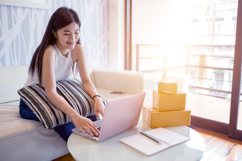 Mujer joven asiática que usa el ordenador portátil que comprueba el producto de la orden imágenes de archivo libres de regalías