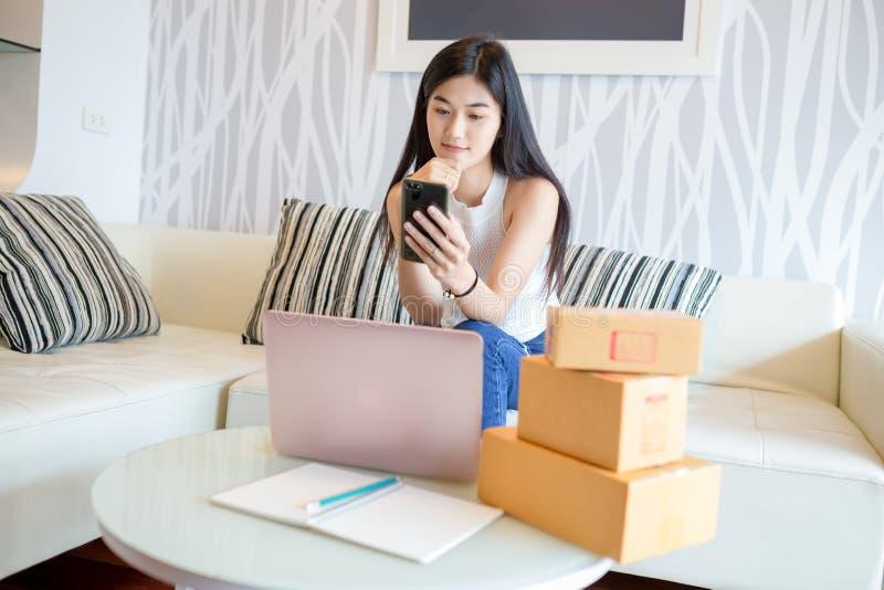 Mujer joven asiática que usa el smartphone que comprueba el producto de la orden en línea foto de archivo