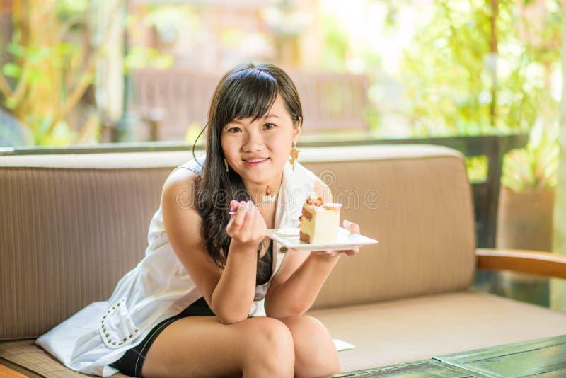 Mujer joven asiática sonriente hermosa que se sienta en el sofá foto de archivo