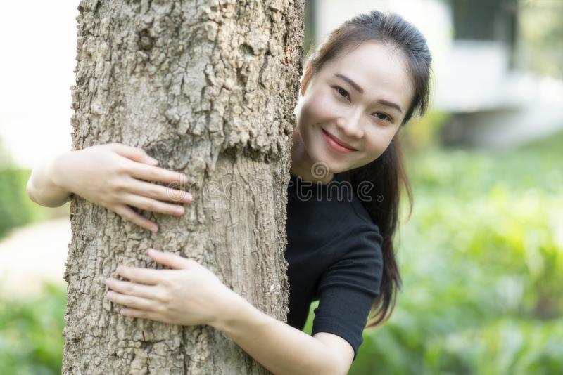 Mujer joven asiática sonriente que abraza el árbol en el parque fotografía de archivo
