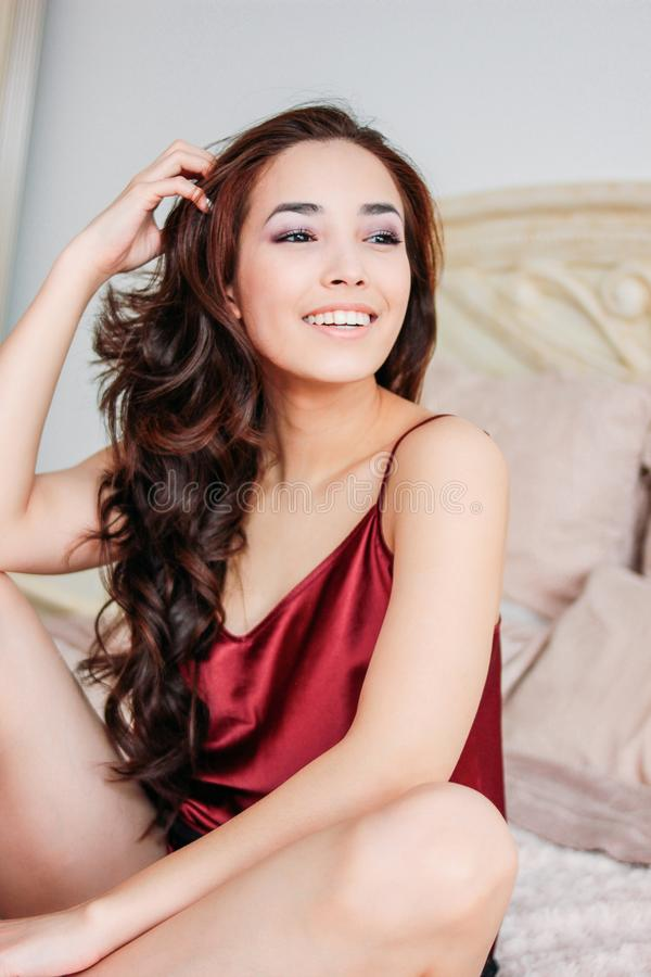 Mujer joven asiática sonriente sensual feliz de la muchacha con el pelo rizado largo oscuro en la ropa interior roja que se sient imagen de archivo